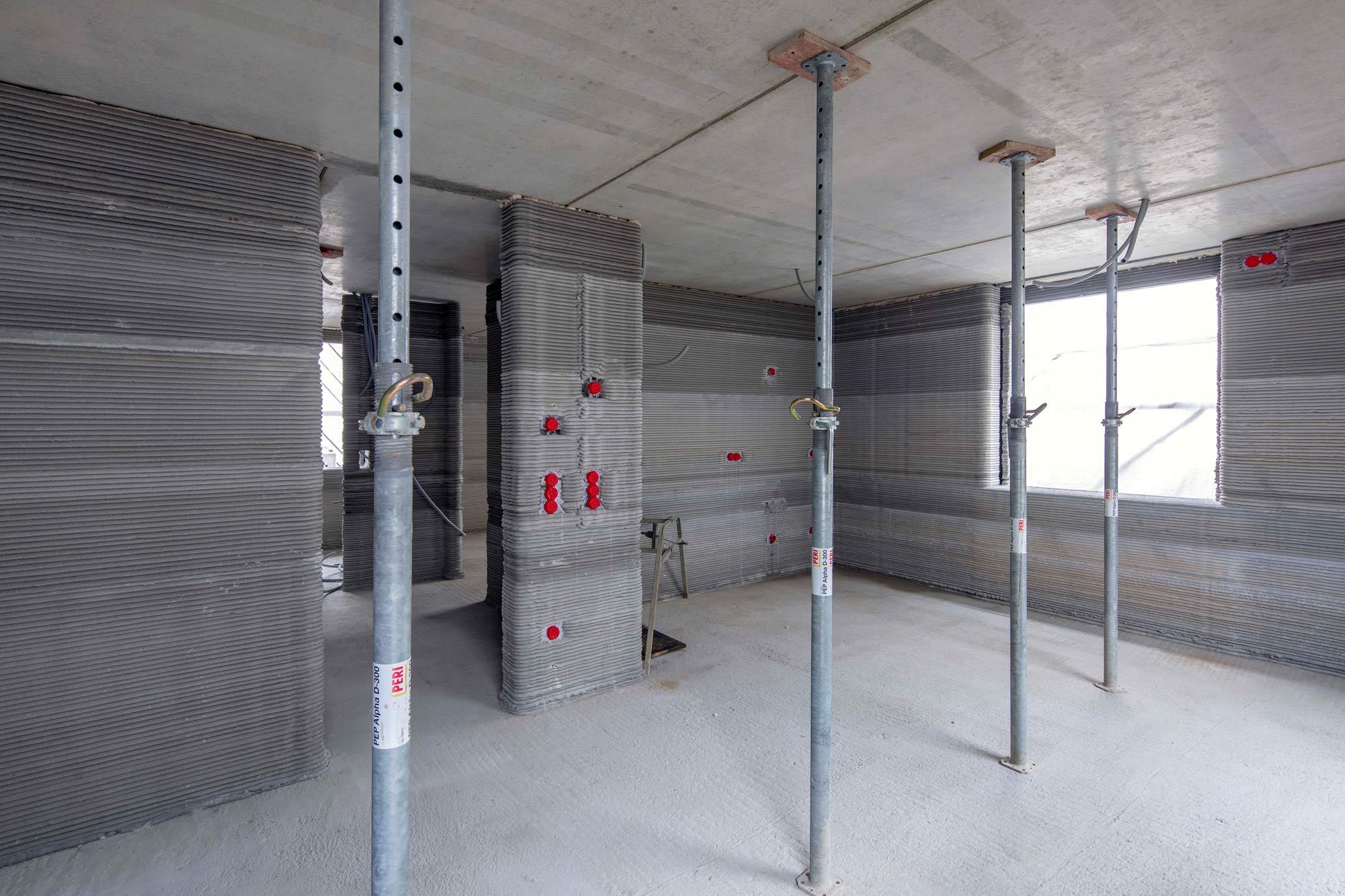 Druck eines Mehrfamilienhauses in Wallenhausen: Die Pläne setzt der 3D-Drucker auf der Baustelle eins zu eins um - inklusive der Aussparungen für die Steckdosen.